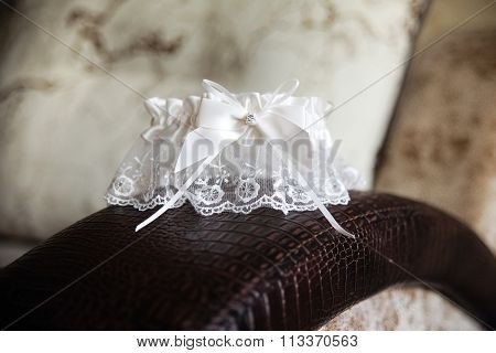 Wedding garter white with pendant on a leather sofa the morning of the bride