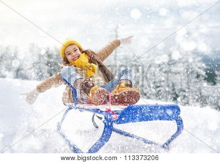 Child sledding. Little girl enjoying a sleigh ride. Child girl riding a sledge. Child plays outdoors in snow. Outdoor fun for family winter vacation.