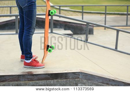 one young skateboarder legs and skateboard at skatepark