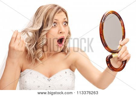 Young enraged bride looking at her hairstyle in a mirror isolated on white background