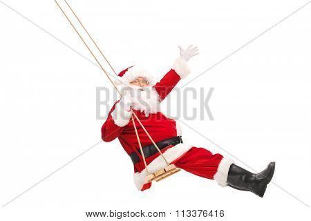 Full length profile shot of Santa Claus swinging on a wooden swing isolated on white background