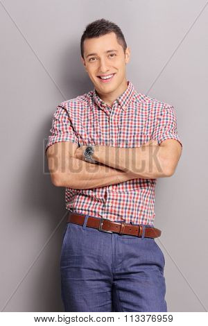 Vertical shot of a confident young man in casual clothes leaning against a gray wall and looking at the camera