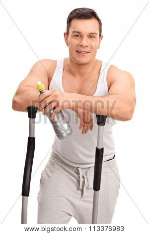 Vertical shot of a young man leaning on the handles of a cross trainer and holding a water bottle isolated on white background