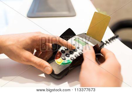 hand entering pin code to bank terminal
