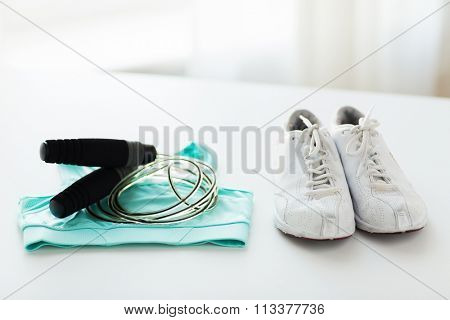 close up of sports top, sneakers and skipping rope