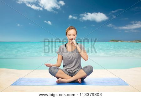 woman meditating in lotus yoga pose on beach
