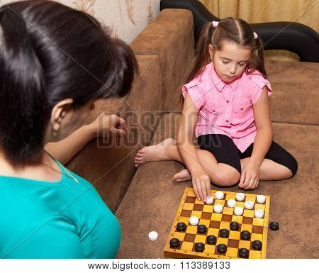 Little Girl Playing Draughts With Her Mother