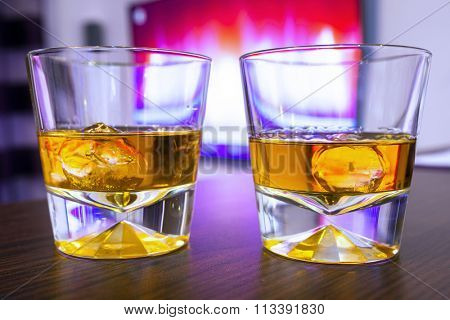 Glasses of scotch whiskey on ice at the tv