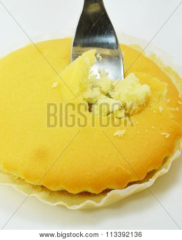 fork stab in butter cake on white background