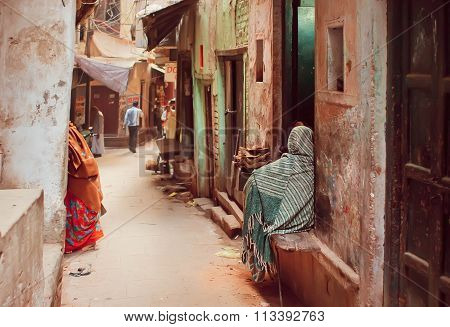 Poor People In Long Traditional Scarfs Sitting On The Grunge Street Of Ancient Indian City