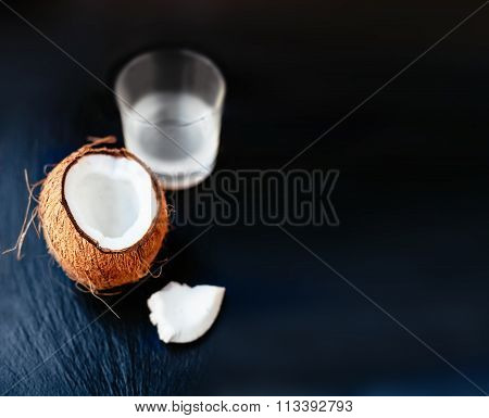 Cracked Coconut  With Coconut Milk In A Glass. Coco Nut Cut In Half.on A Vintage Wooden Background W