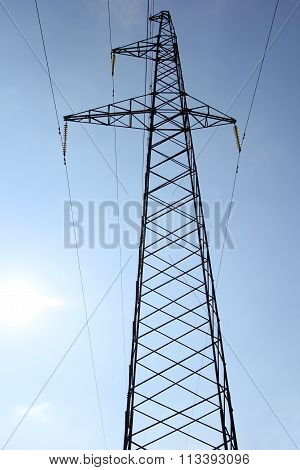 High Voltage Power Pylons Against Blue Sky