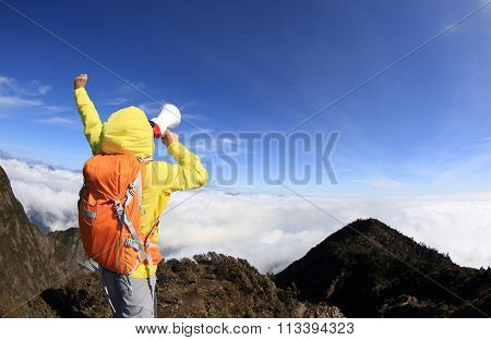 young woman backpacker shouting with loudspeaker on beautiful mountain peak