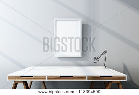 Detail of Office Furniture - Drafting Desk with Wooden Drawers, Modern Table Lamp and Empty Picture Frame in Modern Sparsely Decorated Office Lit by Sunshine from Large Side Window