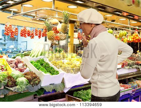 Woman buys fresh fruits and vegetables in market. Woman looking to raw fruits and vegetables in supermarket