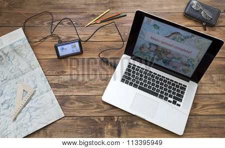 Preparing for trip Wooden desk at home laptop with map
