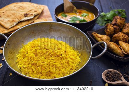 Indian Chicken Pilau Rice In Balti Dish Served With Tikka Masala Curry And Side Dishes