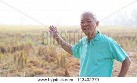 Happy Asian Senior Modern Farmer Smiling In Front Of Harvested Rice Field