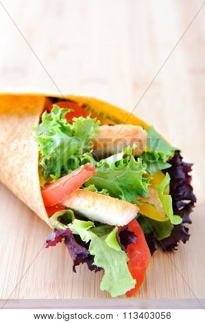 Chicken strips with fresh salad, bell peppers and tomato slices wrapped in a tortilla