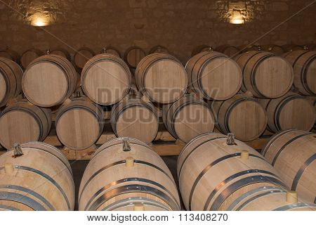 Wine Barrels Stacked In The Old Cellar Of The French Winery.