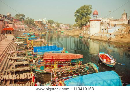 Colorful Riverboats Floating On The Quiet Water River Of Indian City With Historical Houses