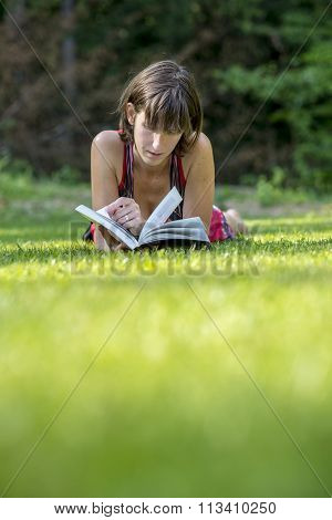 Young Woman Lying In Green Grass Reading A Book