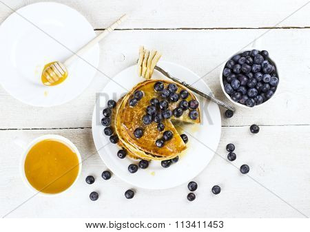 Heap Of Pancakes The Slices Of Pancakes Watered With Honey And Blueberry, Cut Off On A Fork On A Whi