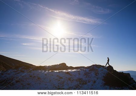 Silhouette Of A Climber On A Mountain Ridge.