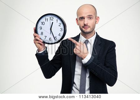 Handsome young business man in black suit and tie pointing on clock over white background