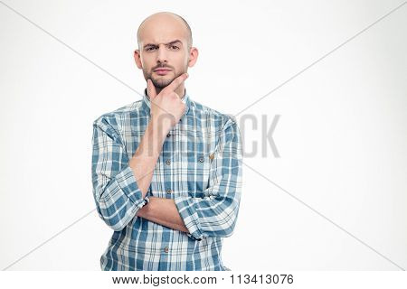 Pensive doubtful young man in checkered shirt holding hand on his chin over white background