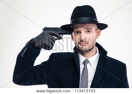 Despaired man in black coat, hat and gloves put gun to his temple over white background