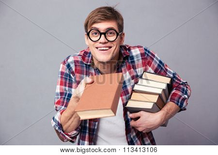 Playful happy young man in checkered shirt and funny round glasses giving youn a book over grey background