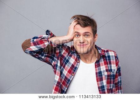 Close up of embarrassed young man in checkered shirt scratching head and looking confused over grey background
