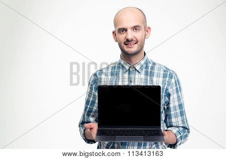 Charming smiling young man in checkered shirt holding blank screen laptop over white background