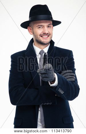 Cheerful handsome investigator in black coat, hat and gloves pointing on you over white background