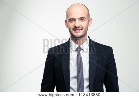 Portrait of happy handsome young businessman in black suit and tie over white background