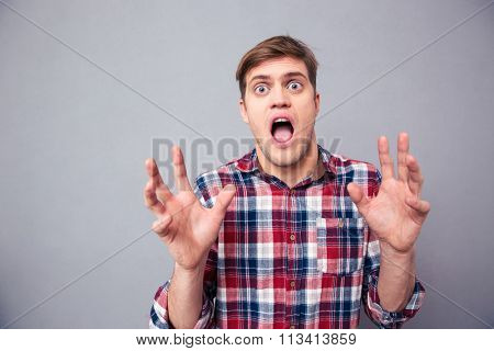 Portrait of terrified frightened young man in checkered shirt screaming with open mouth over grey background