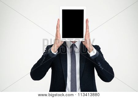 Businessman in black suit and white shirt holding blank screen tablet in front of his head over white background