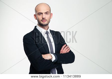 Handsome confident young businessman in black suit standing with folded hands over white background