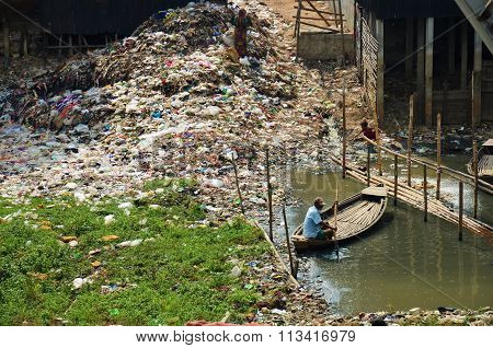 Man in a boat by a mountain of rubbish