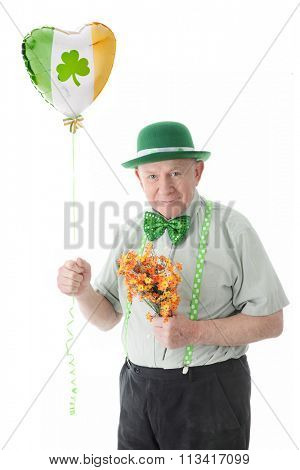 A senior Irish man happily bringing flowers and a balloon for his lady on St. Patrick's Day.  On a white background.