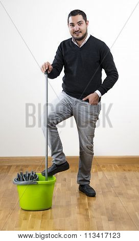 Full length of an adult man mopping floor at home.