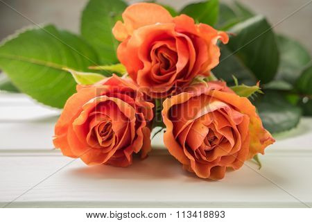A Bouquet Of Orange Roses On Wooden Table. Copy Space