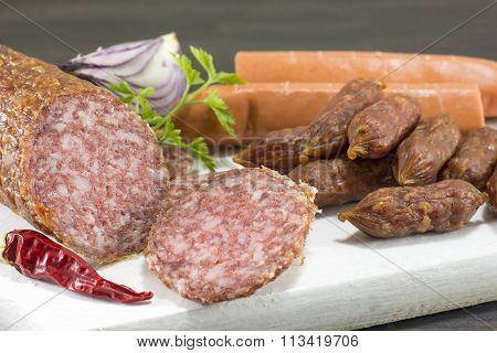 Sausages And Hotdogs On A White Cutting Board