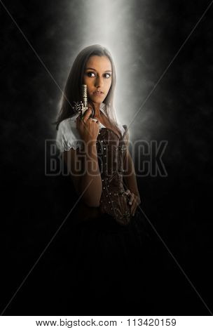 Young Brunette Woman Wearing Old Fasioned Western Costume with Corset Holding Antique Pistol and Looking Suspiciously to the Side in Dark Studio Under Spotlight with Copy Space