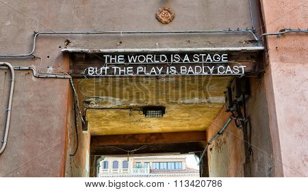 Quotation over a doorway entrance to a thoroughfare in Venice, Italy saying - The world is a stage but the play is badly cast