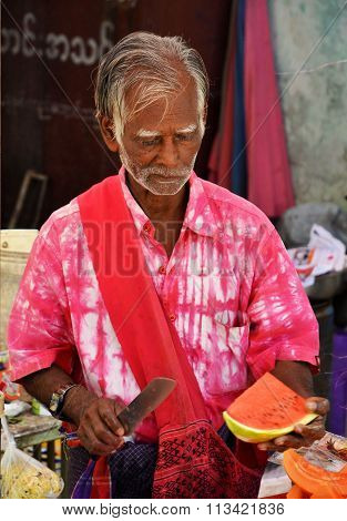 Local Man In Pink Cutting Watermelon On Street In Yangon