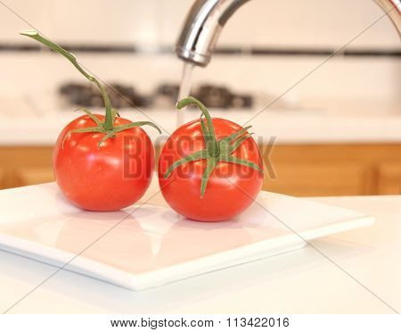 Washing tomatoes in a kitchen.