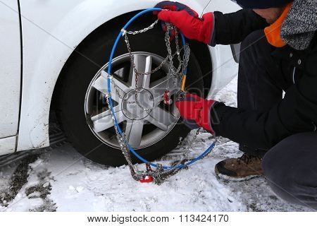 Automobile Mechanic Assembles The Snow Chains In The Car Wheel In Winter On Snow