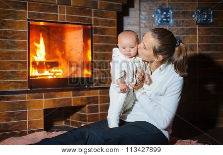 Mother Kisses Daughter At The Fireplace
